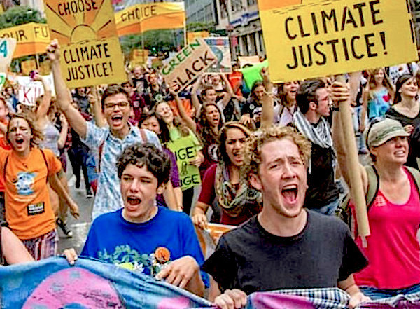 Colorfully dressed students with placards take over a downtown LA street shouting slogans and demanding climate justice for their doomed generation