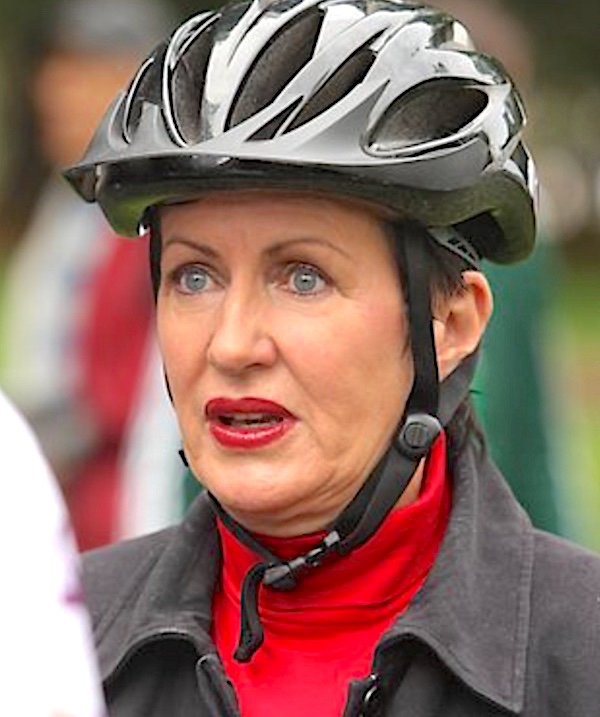 A woman with blue eyes wearing a bicycle helmet. pic