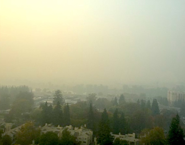 This shows a thick blanket of forest fire smoke obscuring the view of downtown Sacramento. Photo.