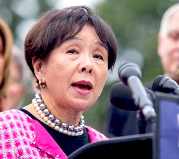 An Asian-American older woman in front of a microphone giving a commencement address.