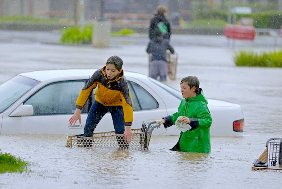 kids in raincoats playing with a shopping cart in a flooded parking lot