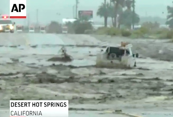 a heavy duty truck bobbing up and down in flash flood while a rescue vehicle is arriving