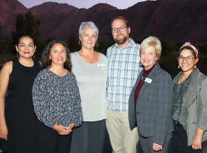 Six smartly dressed people, five women and one man, pose in the twilight with desert mountain in the background. Photo.