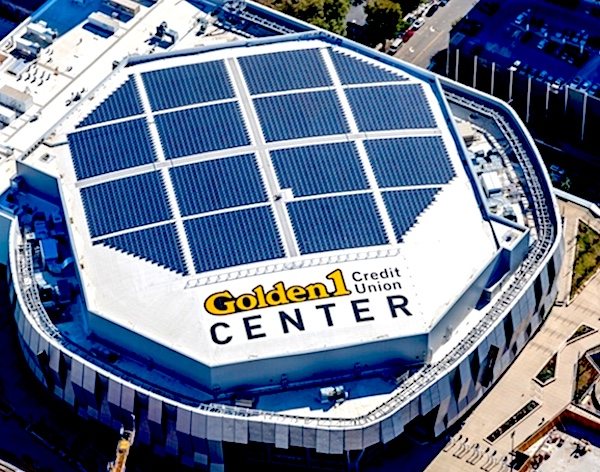 An aerial view of Golden One Center, where the Sacramento Kings play. The rooftop is a vast geometric pattern of dark blue solar panels. Photo.