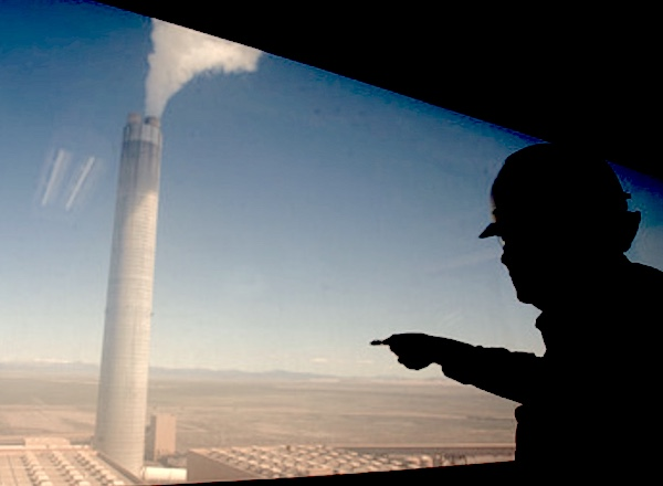 Photo of a worker in a hardhat standing on a platform high above the desert pointing at a colossal smokestack spewing heat-gasses high into the atmosphere.