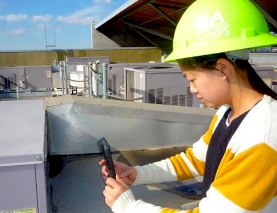 A high school student in a bright yellow hard hat on the roof of her school using a device to measure the the energy usage of the building. photo.