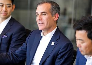Los Angeles Mayor Eric Garcetti sitting at a table, talking to a group of businesspeople