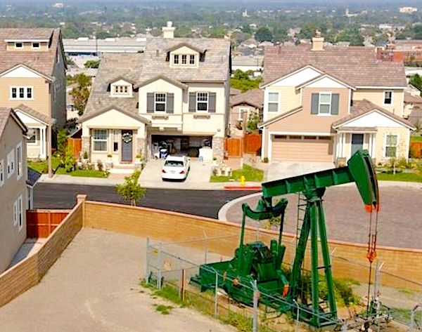 An oil rig looks out-of-place on an open lot in a suburban subdivision.