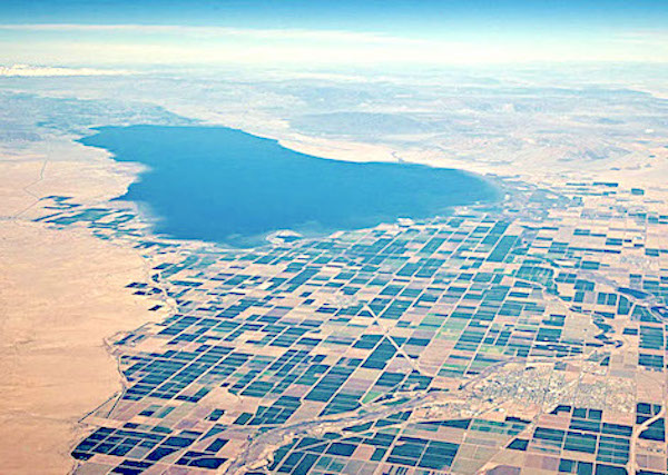 Aerial view of the green-blue Salton Sea, which looks like a big pond in the vast desert, not like an actual sea. Photo.