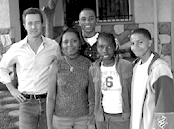 Actor Edward Norton with a family in front of small home. photo