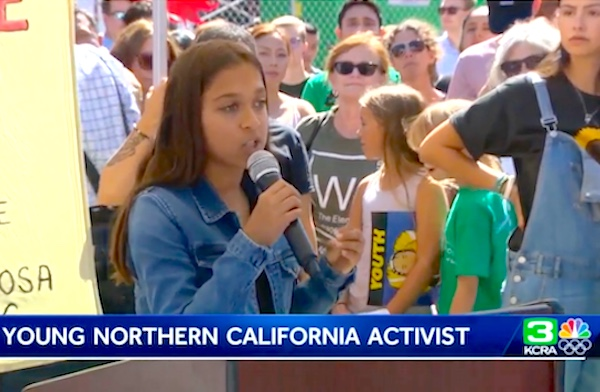 A 13 year old girl outside speaking to a crowd of young climate protesters. Screen capture from local television news.