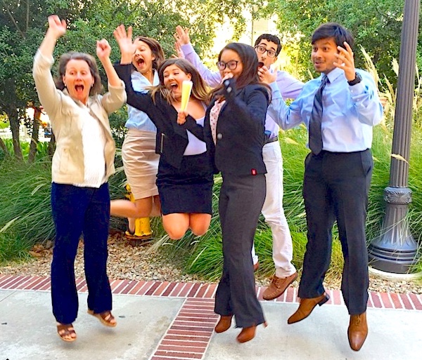students in business attire outside an office building jumping for joy with big smiling faces. photo