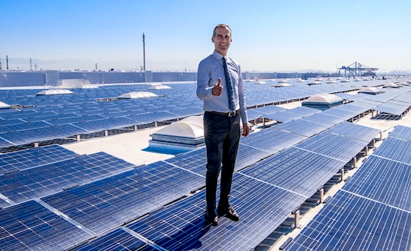 Photo of LA Mayor Eric Garcetti standing on a solar panel and giving the thumbs up.