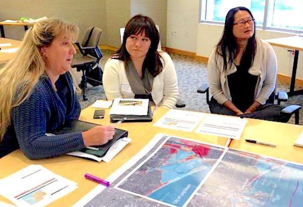Three women sitting around a table at the public library reviewing new maps of LA's coast and talking about what critical infrastructure needs to be upgraded
