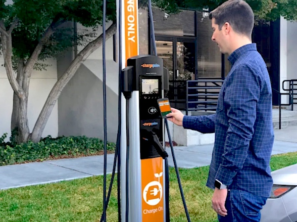 A clean-cut man at an orange-colored electric charging station. He's operating it from a handheld pad.